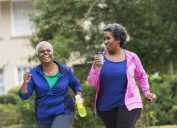 Two senior African American women getting in shape together. They are jogging or power walking on a sidewalk in a residential neighborhood, talking and laughing.