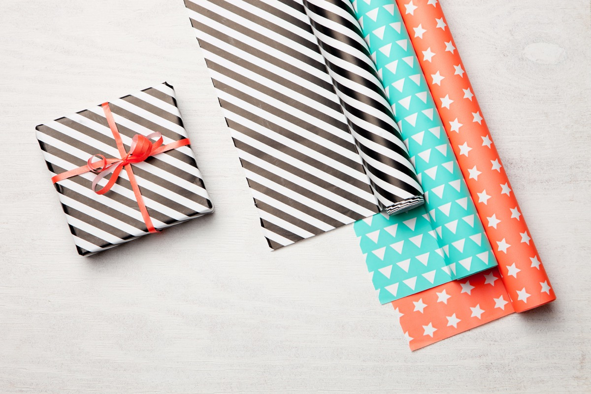 wrapping paper and gift on wooden background