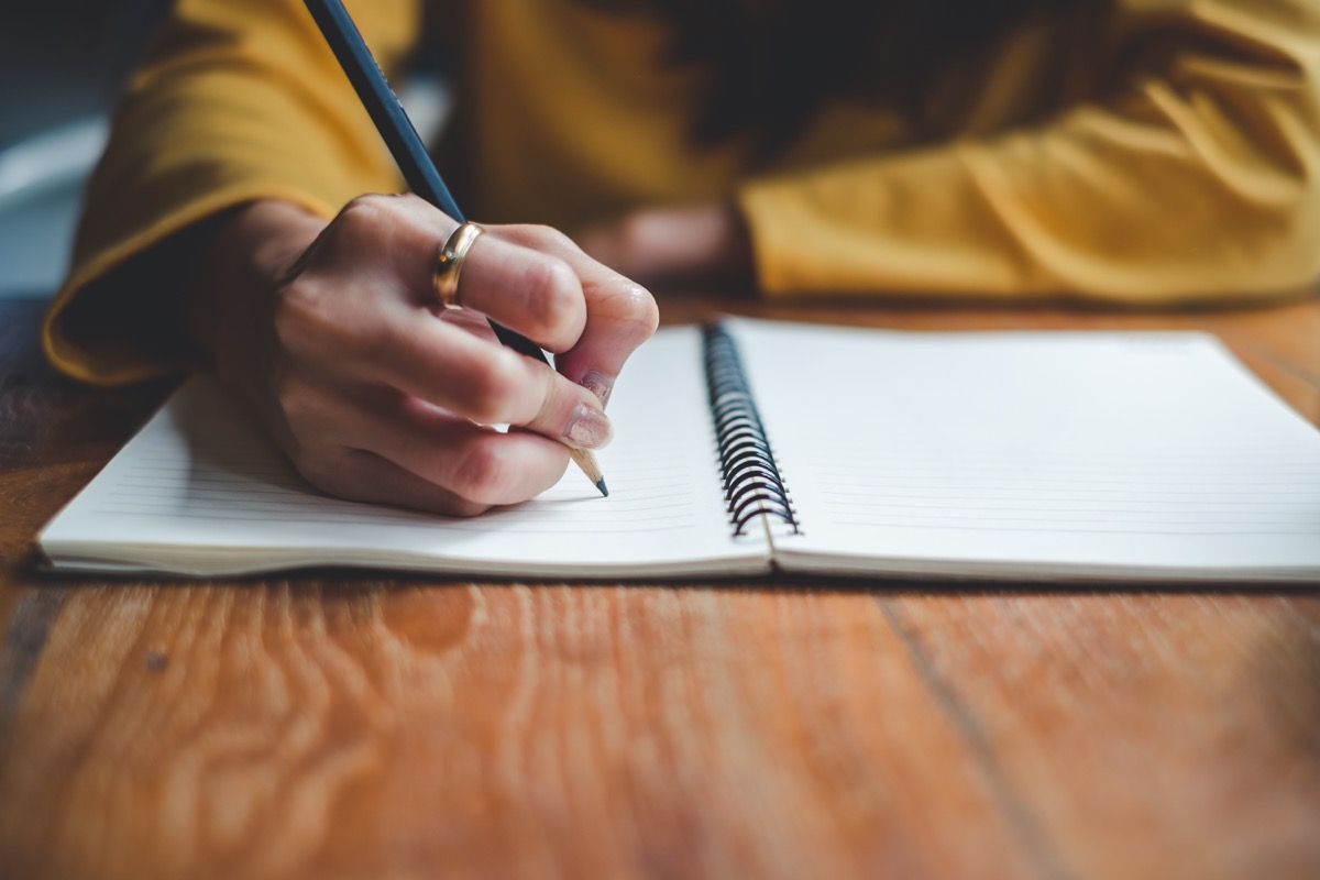 woman writing on a notepad with a pencil