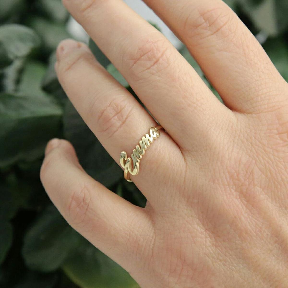 Woman's hans wearing script gold name ring