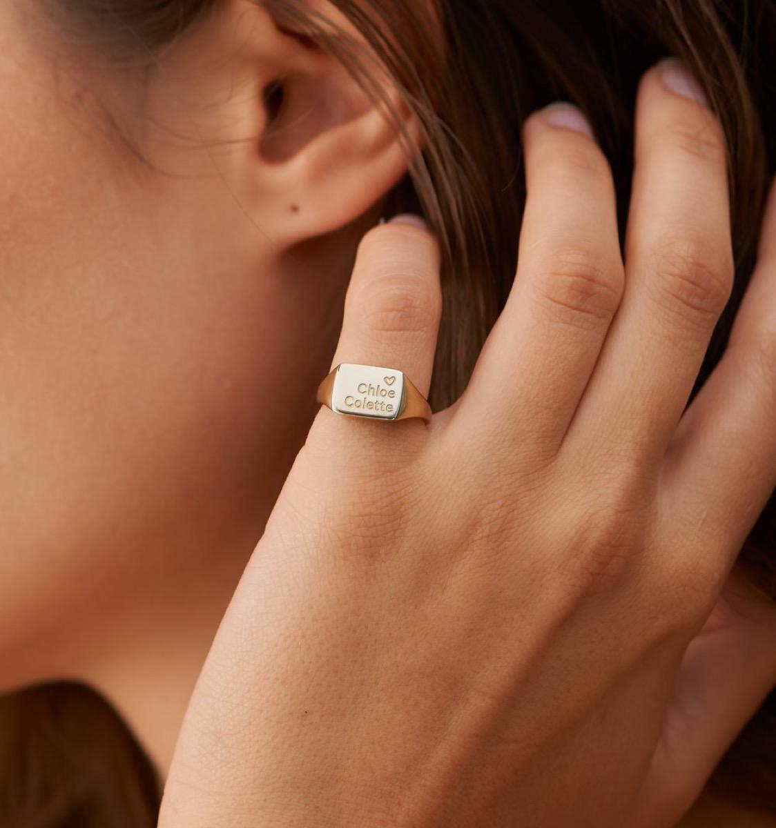 Woman wearing engraved square signet ring