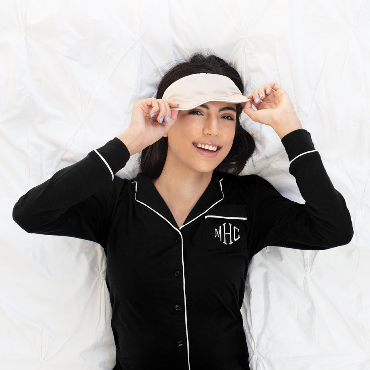 Woman wearing monogrammed pj's and sleep mask
