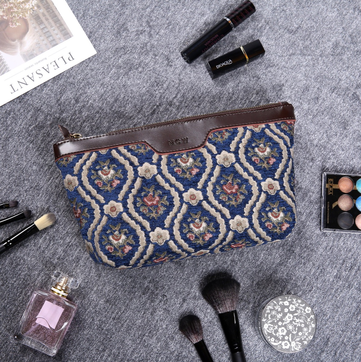 Blue vintage print bag surrounded by beauty products