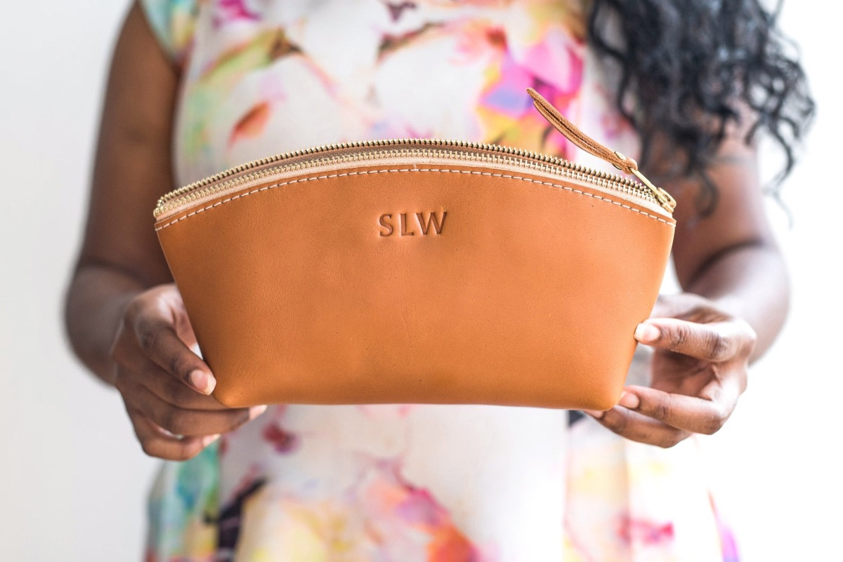 woman holding leather makeup case with monogram