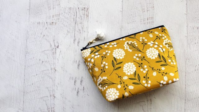 Yellow and white floral bag on wooden floor