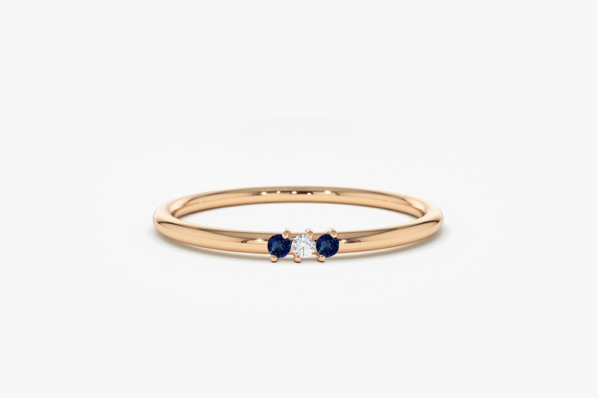 Gold band with diamond flanked by sapphires