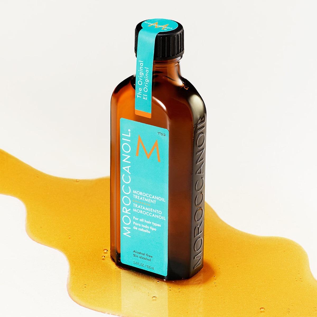 Moroccanoil bottle in pool of argan oil