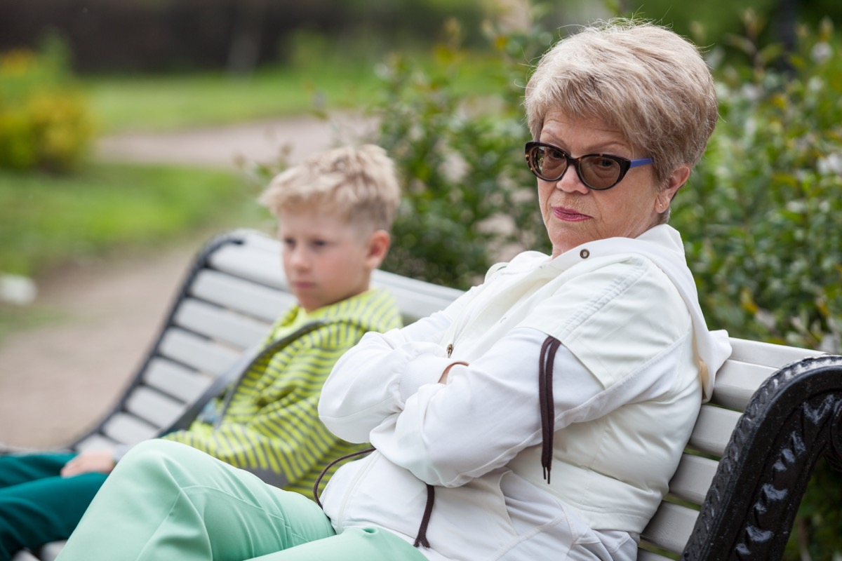 angry white grandmother and grandson on bench