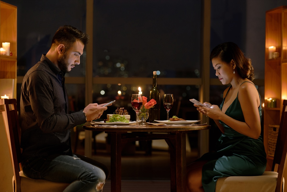 white man and asian woman on phone at dinner
