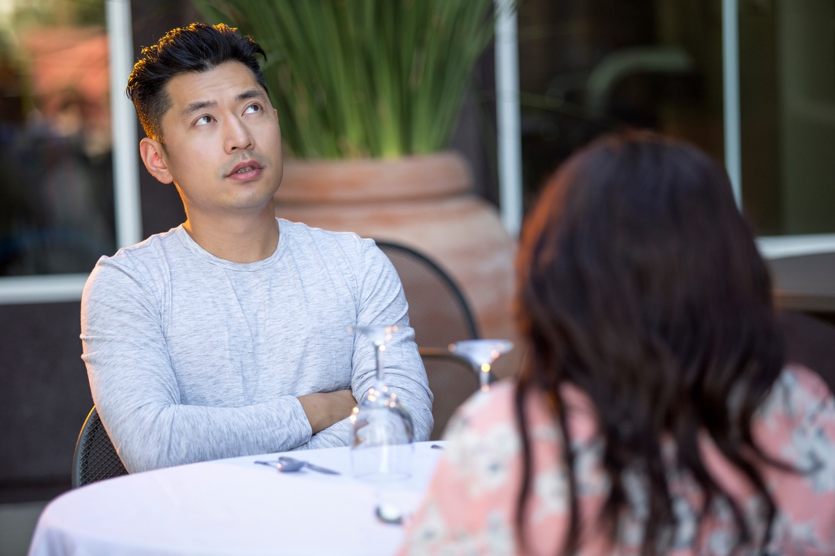 young asian man bored at dinner