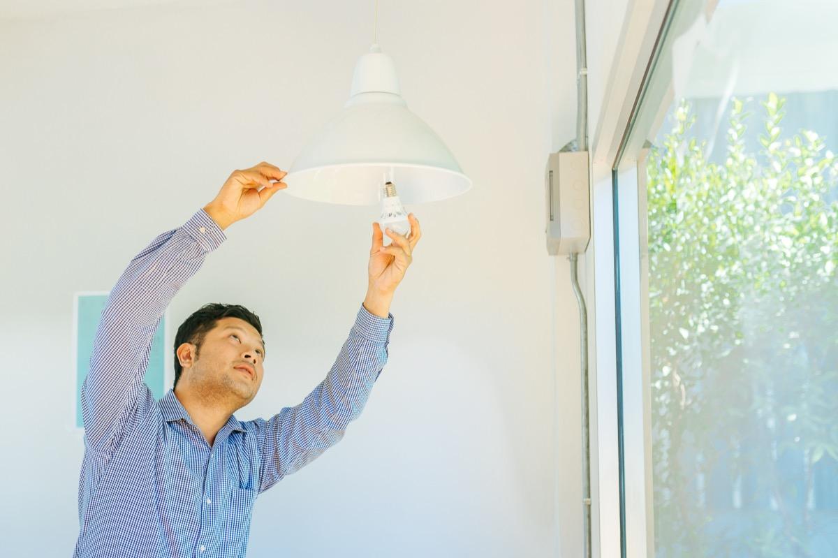 young asian man fixing light bulb