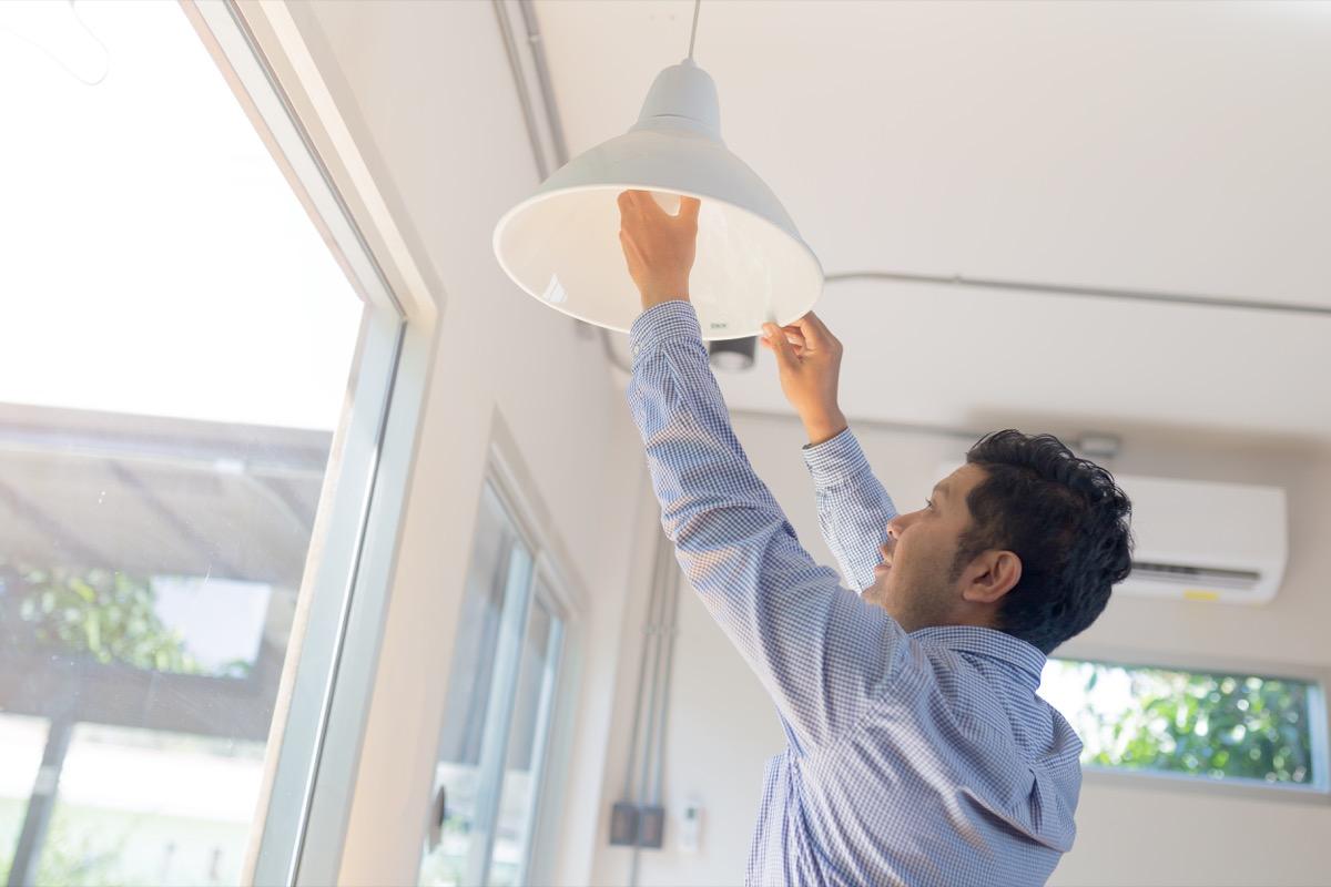 young asian man installing pendant lamp