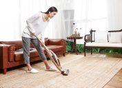 asian woman vacuuming area rug