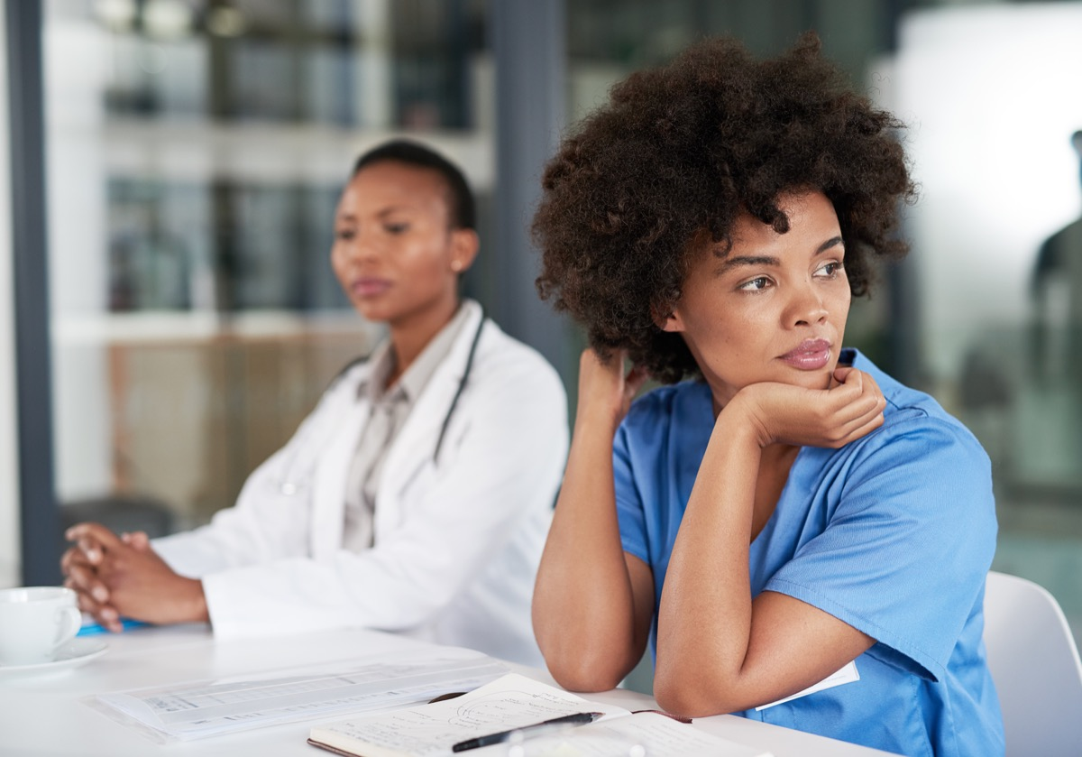 Shot of a young doctor looking bored while sitting in on a meeting at a hospital