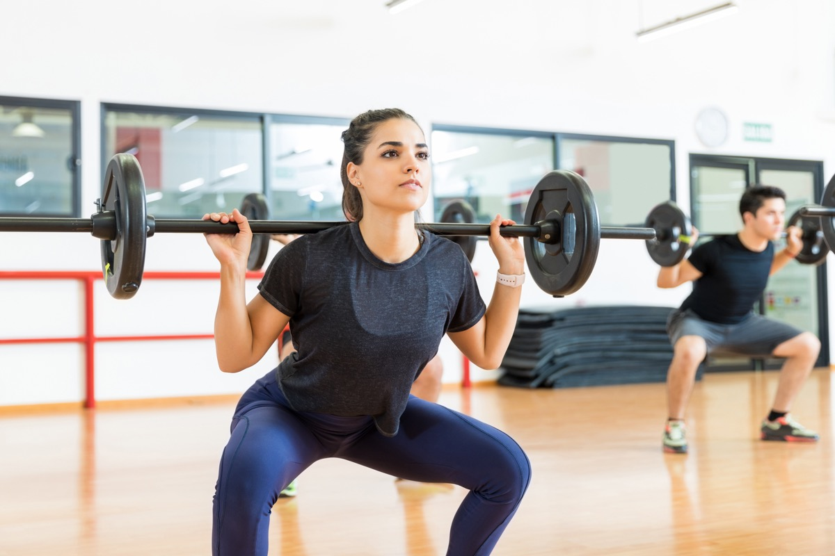 Woman doing a barbell squat in a workout class