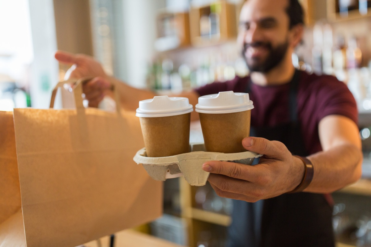 Barista handing over two cups of coffee