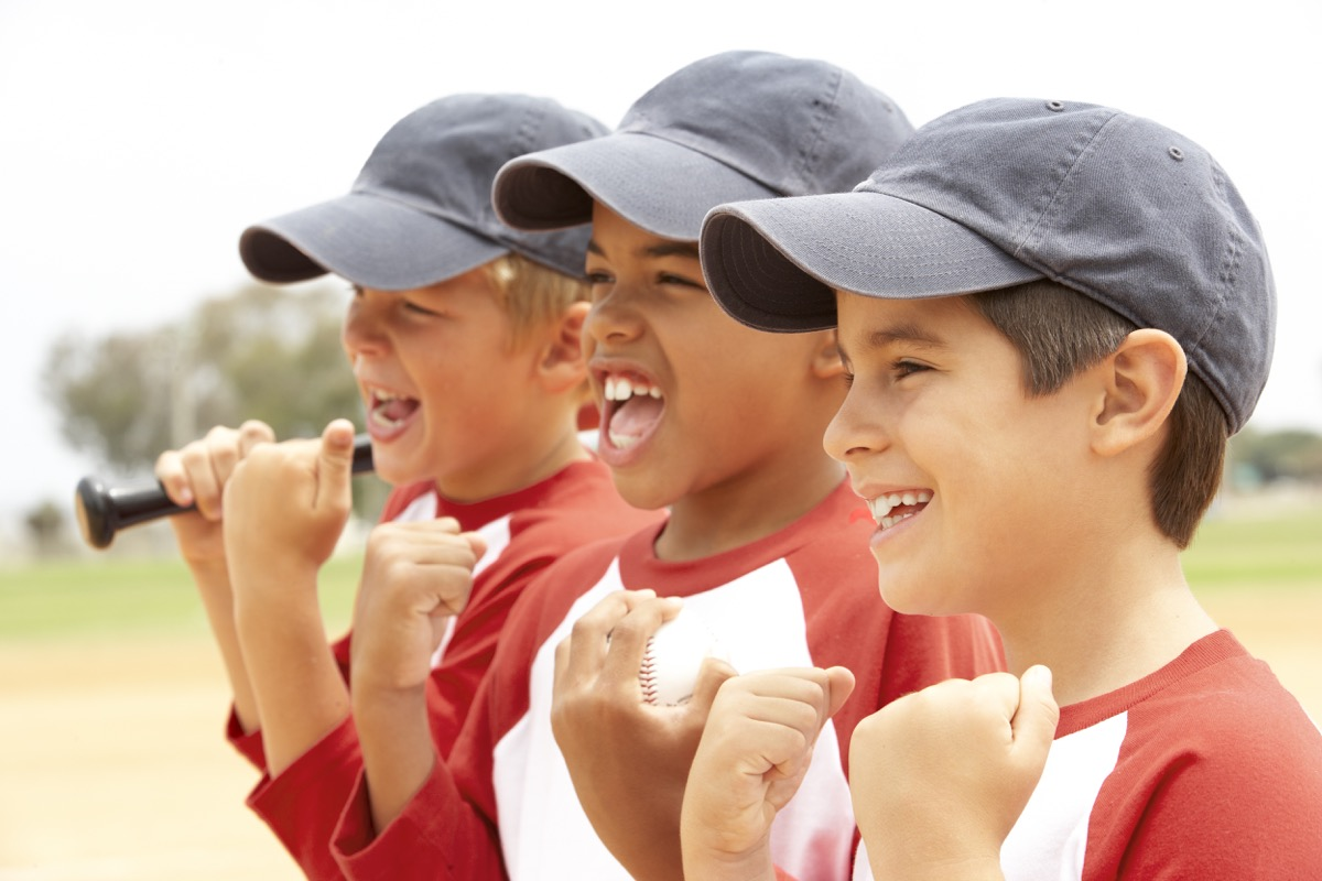 young boys in baseball hats cheering during a game
