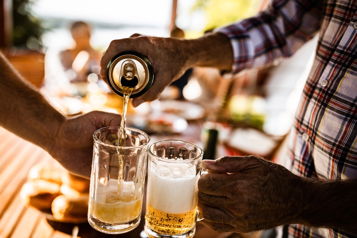 close up of unrecognizable men pouring beer from a can into beer glasses.