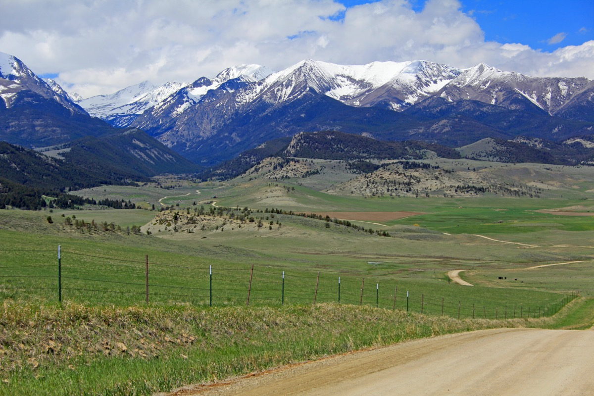 the road from big timber town leading to the crazy mountain range in montana