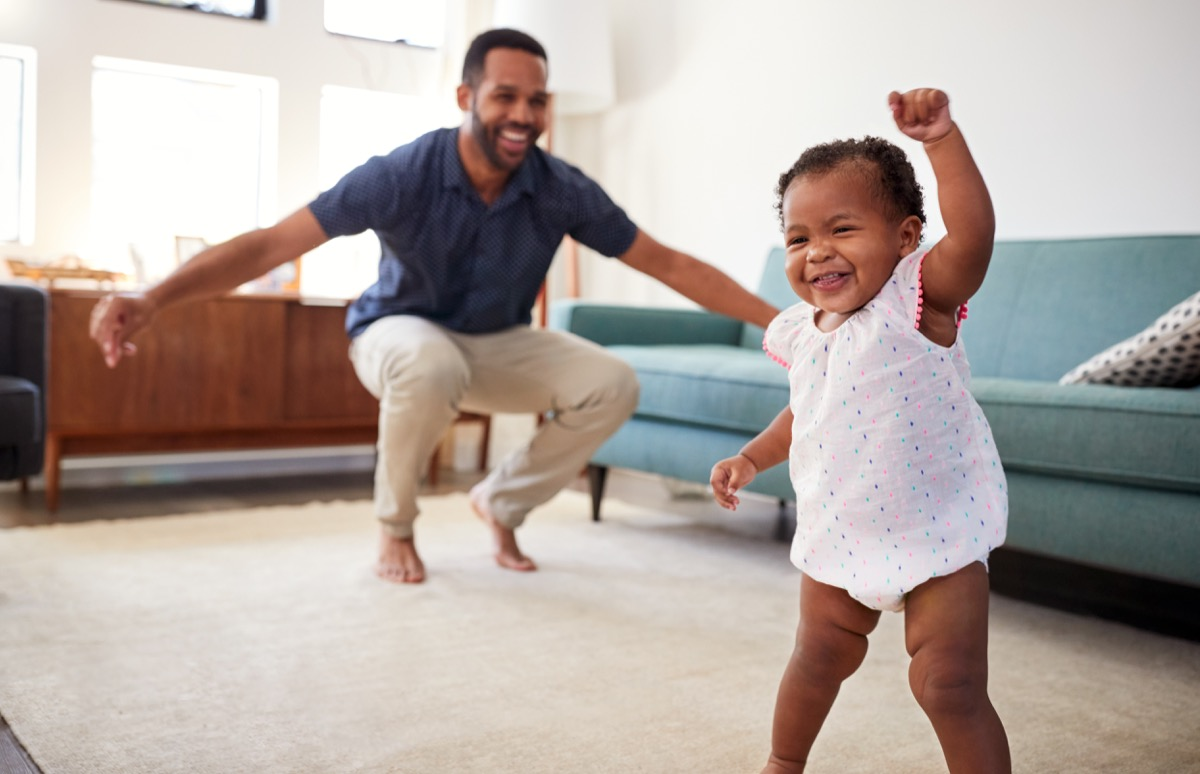 black baby girl walking and playing with dad