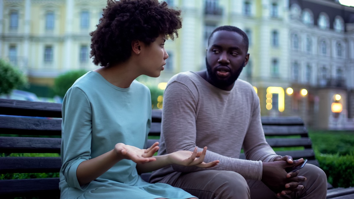 young black couple talking outside on bench