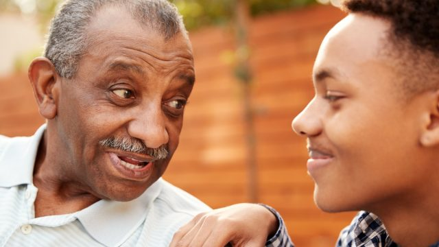 black grandfather talking to teenage grandson