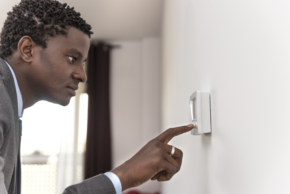 middle aged black man using thermostat