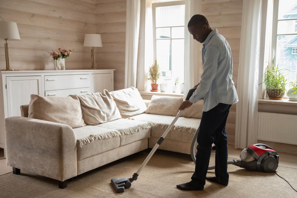 young man vacuuming carpet