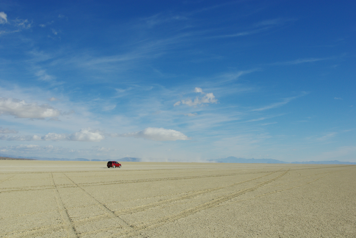 lone car in the middle of black rock desert