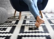 Person resting on black and white patterned rug