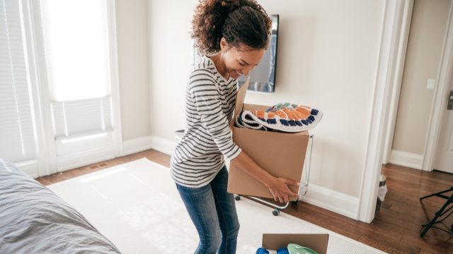 young black woman packing up boxes inside home