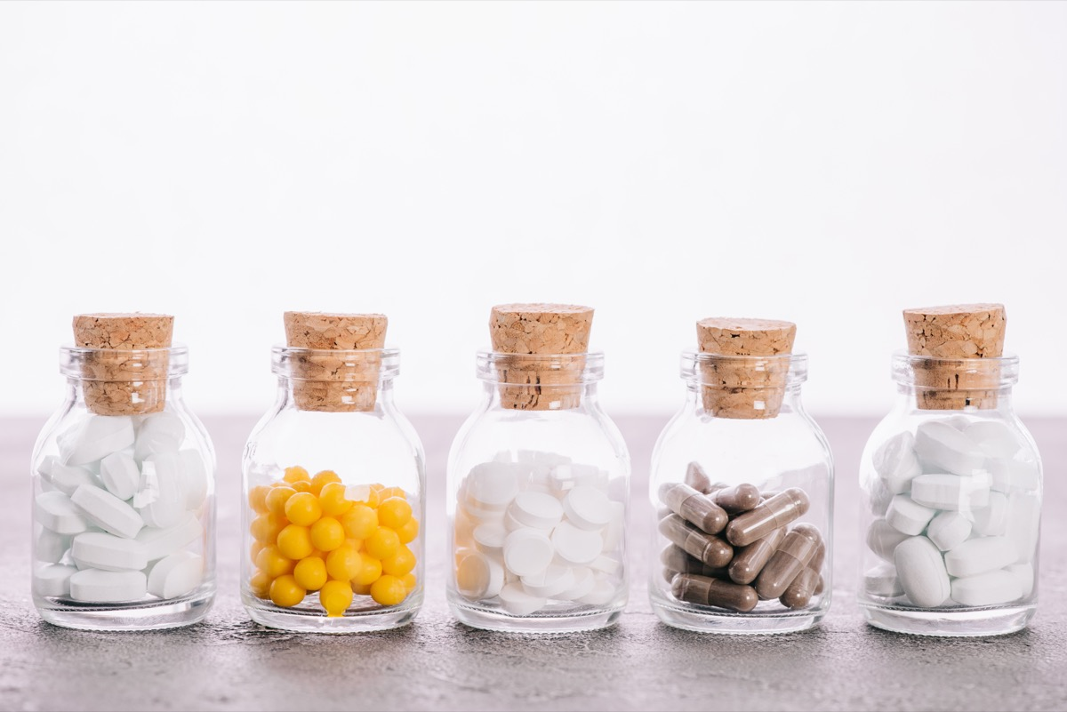 Row of jar bottles filled with various pills including probiotics