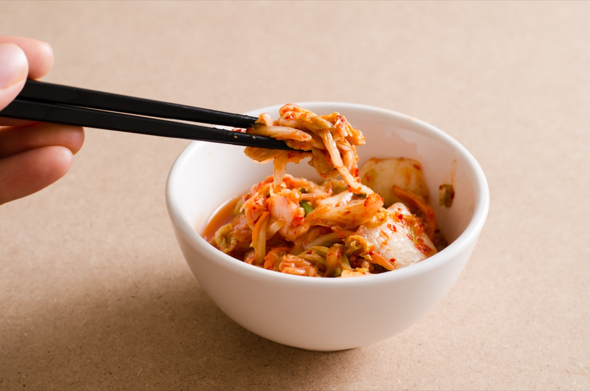 Person eating fermented kimchi with chopsticks
