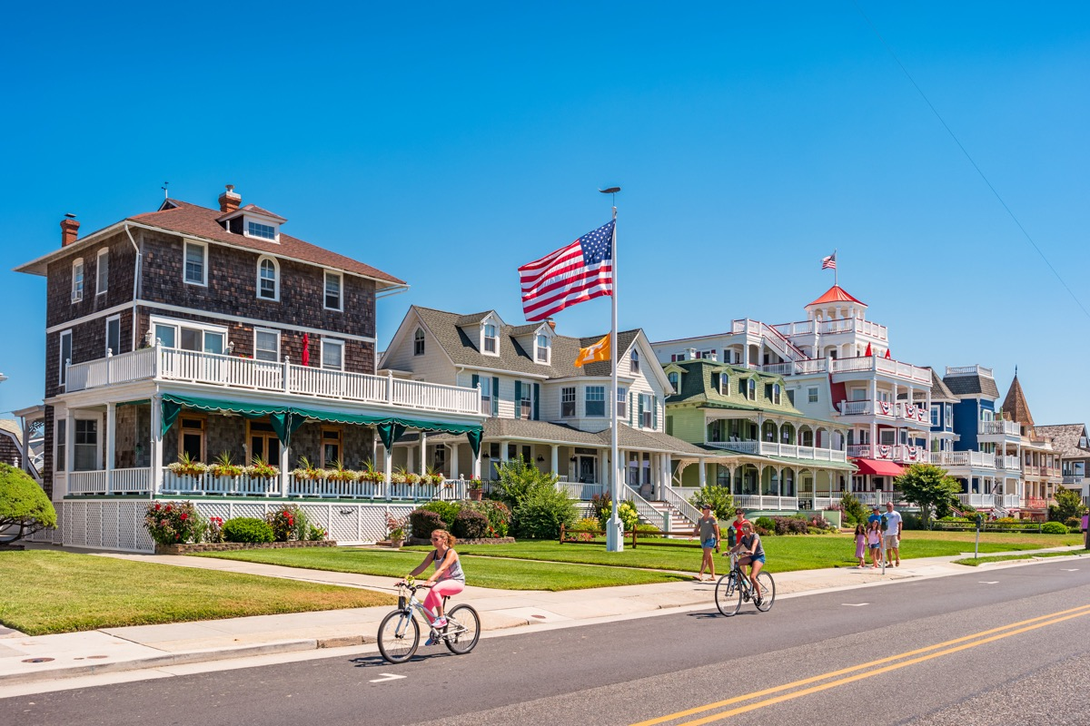 People bike and walk in front of traditional villas in Cape May, New Jersey, USA, on a sunny summer day.