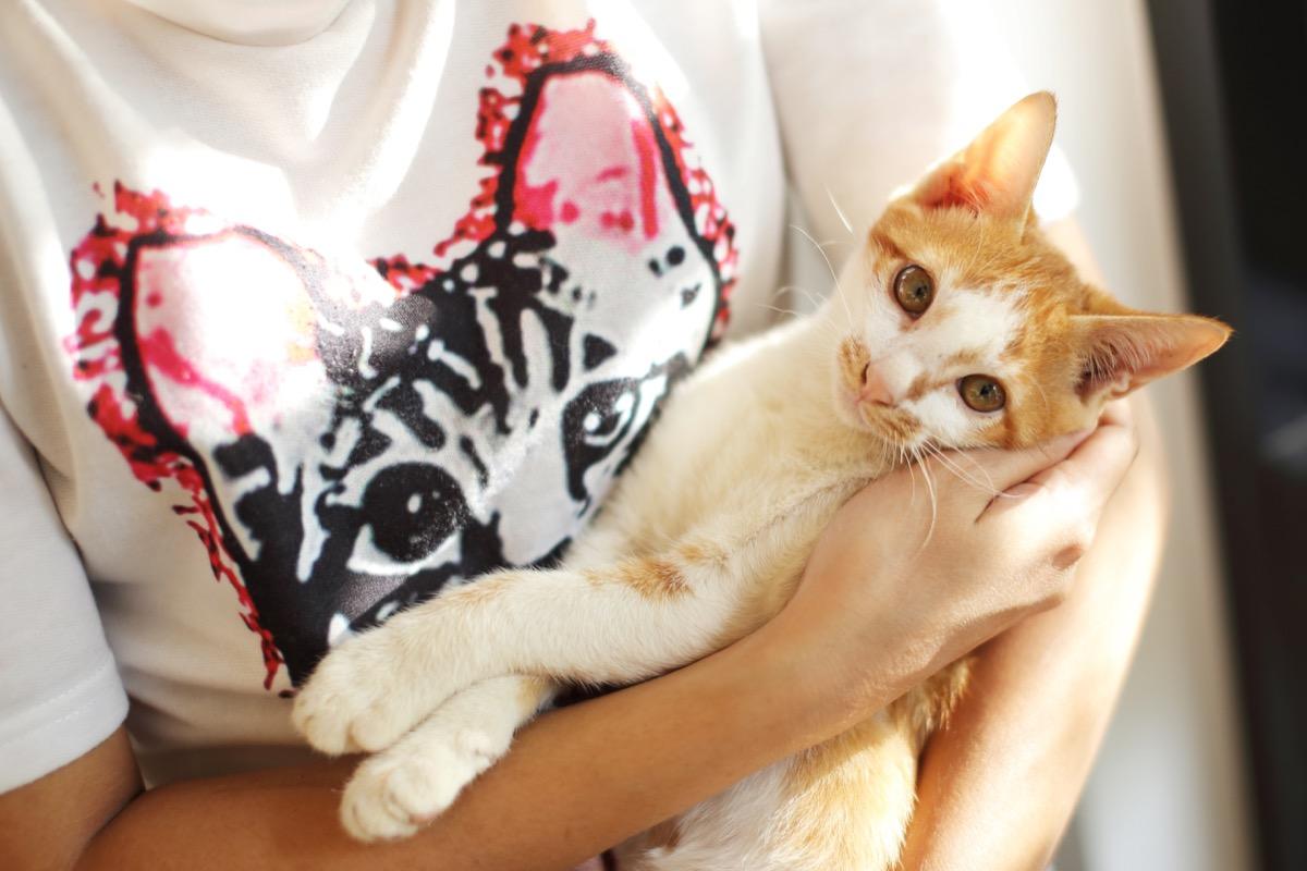 white woman cradling orange cat