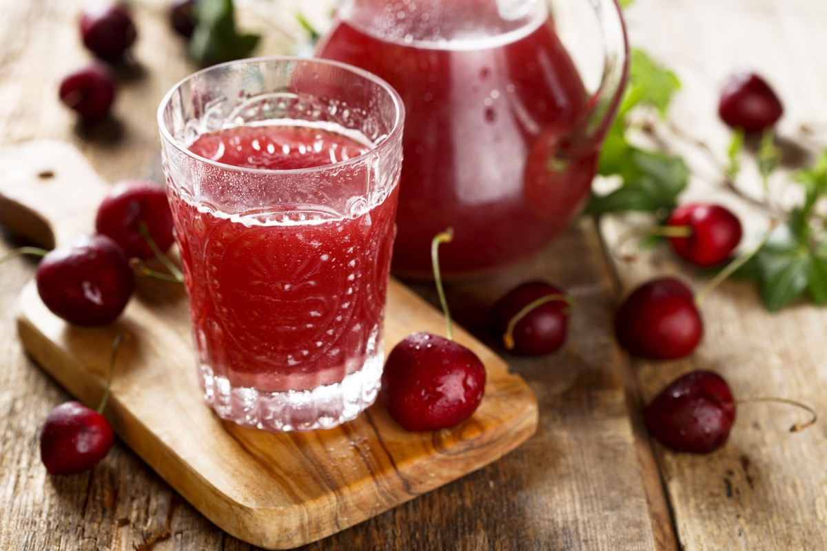 A glass and pitcher of cherry juice