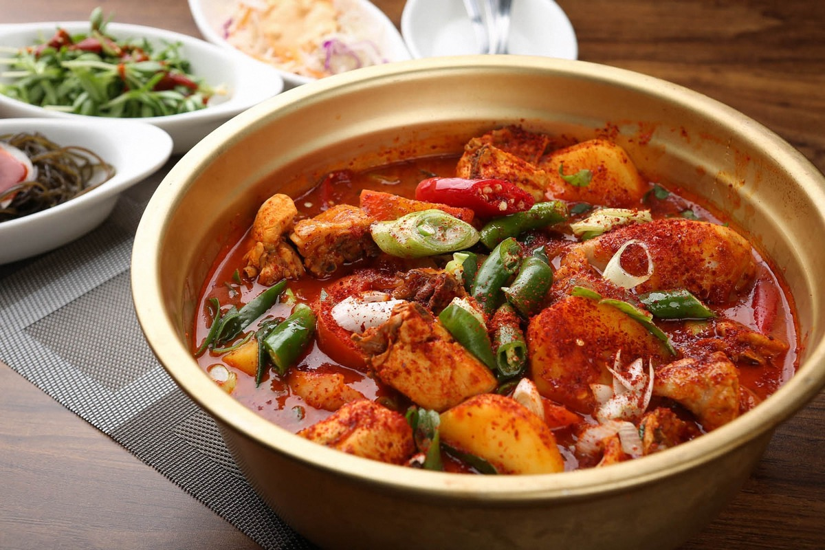 Bowl of spicy dish with chili pepper powder and chicken