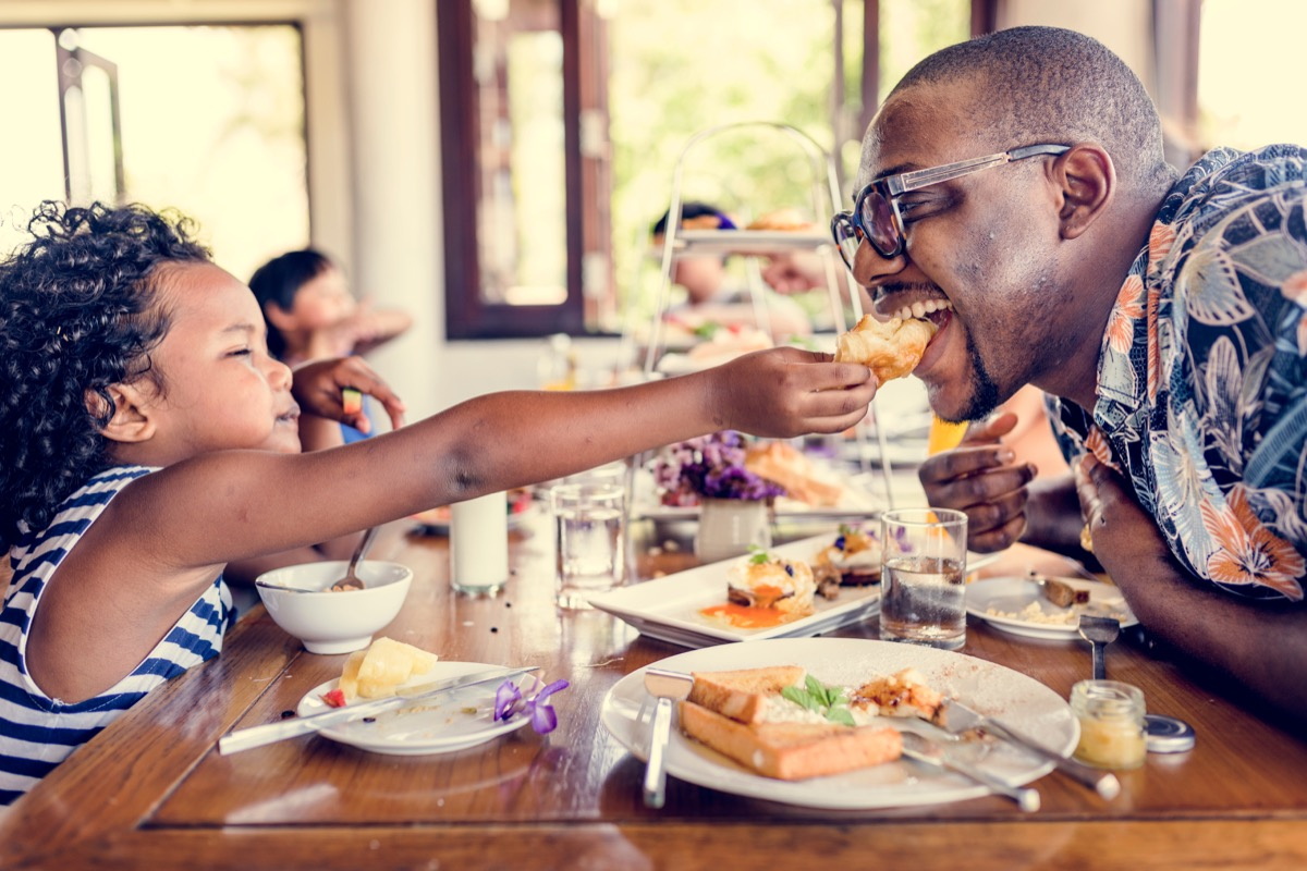 Child feeding his dad at breakfast playful