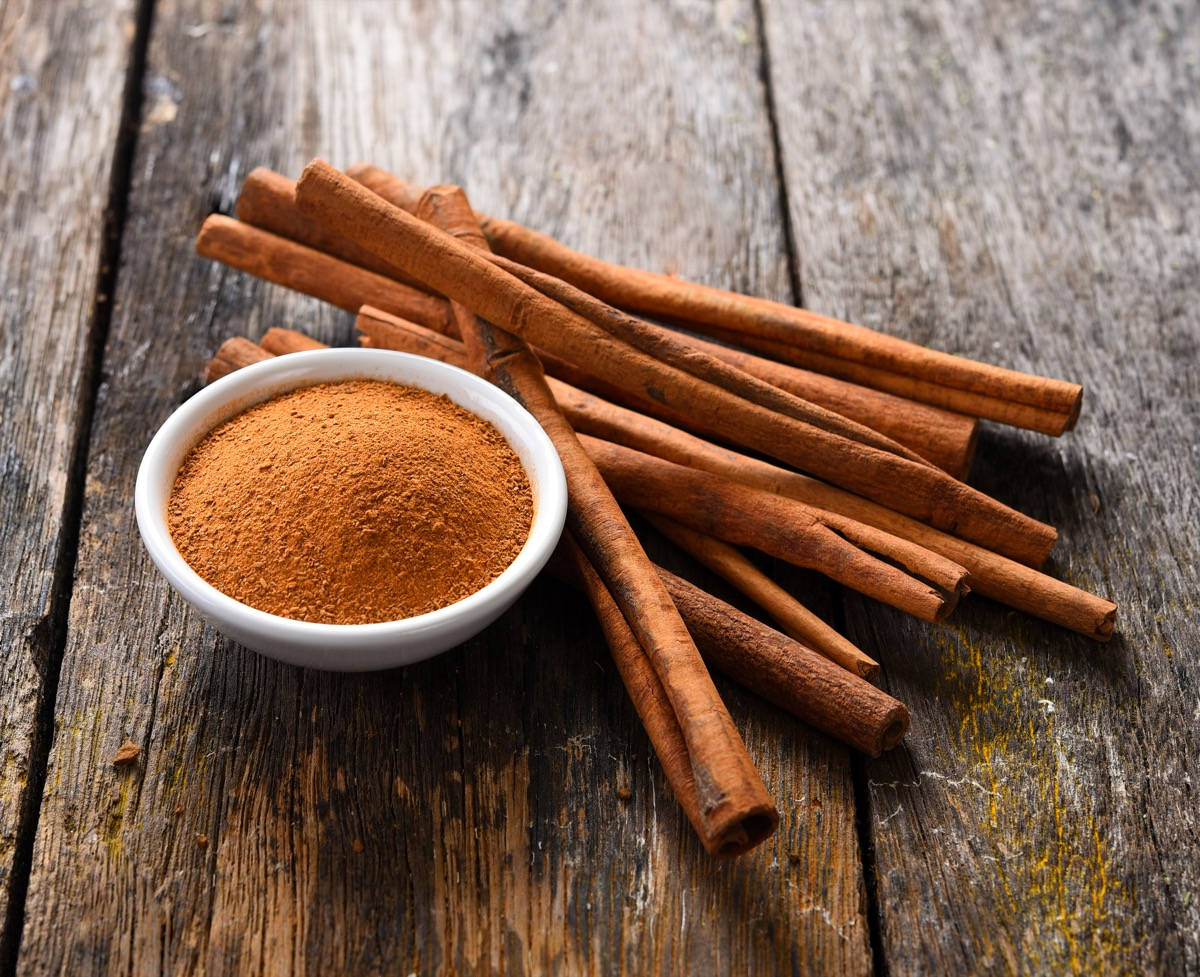 Cinnamon powder and sticks on wooden table