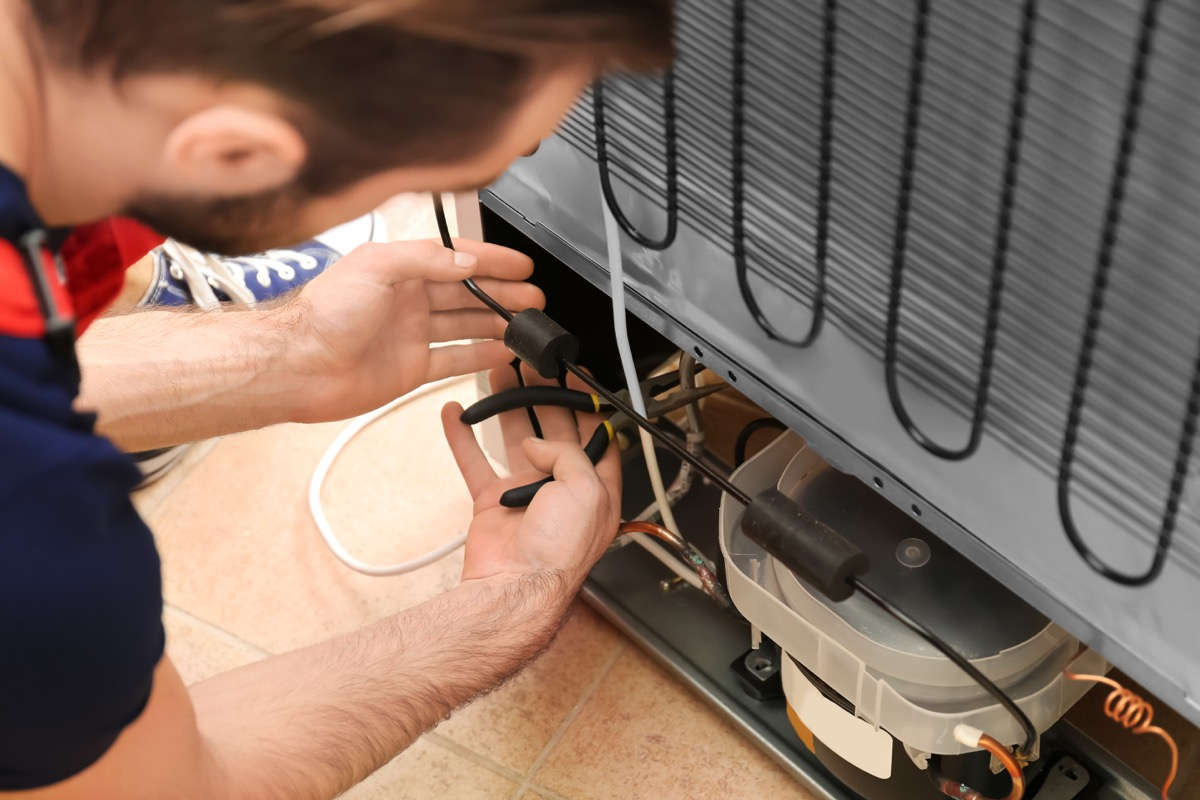 man cleaning refrigerator coil