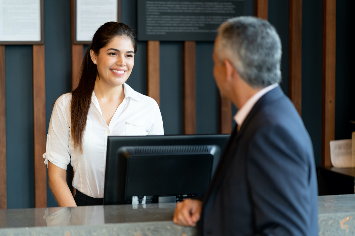 Beautiful hotel receptionist standing behind counter talking to unrecognizable male guest smiling