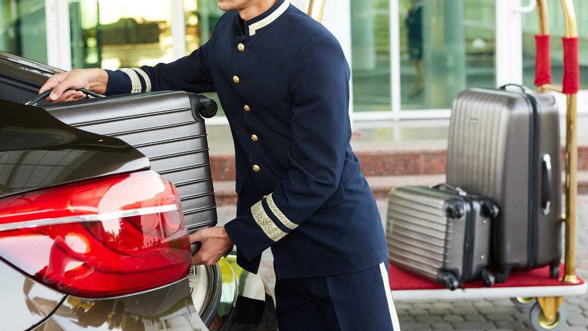bellman loading car with luggages