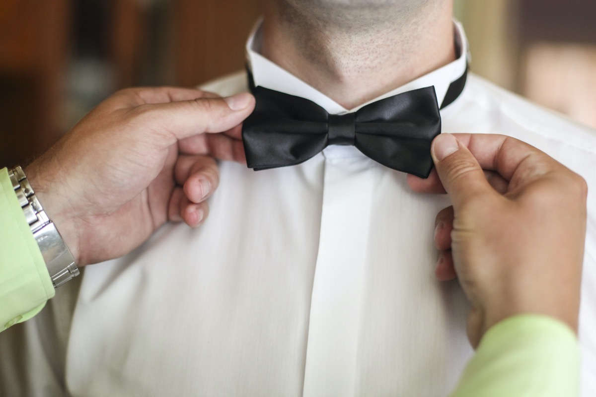 Unrecognizable man fixing bow tie on another man