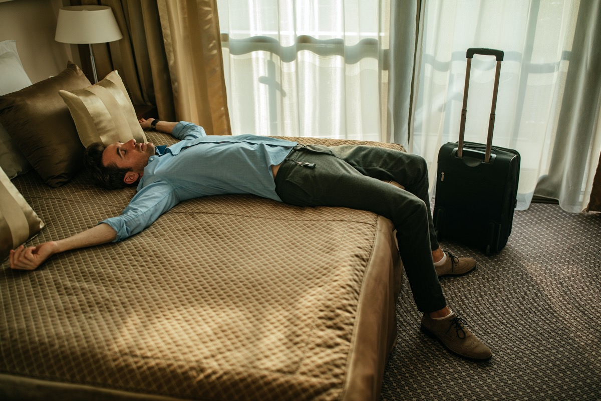 Tired man lying on the bed in a hotel room