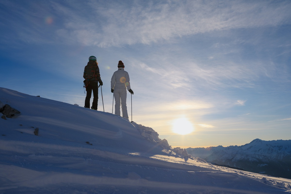 Friends skiing. Snow skiers skiing at sunny ski resort, sunset Dolomites mountain in Italy.