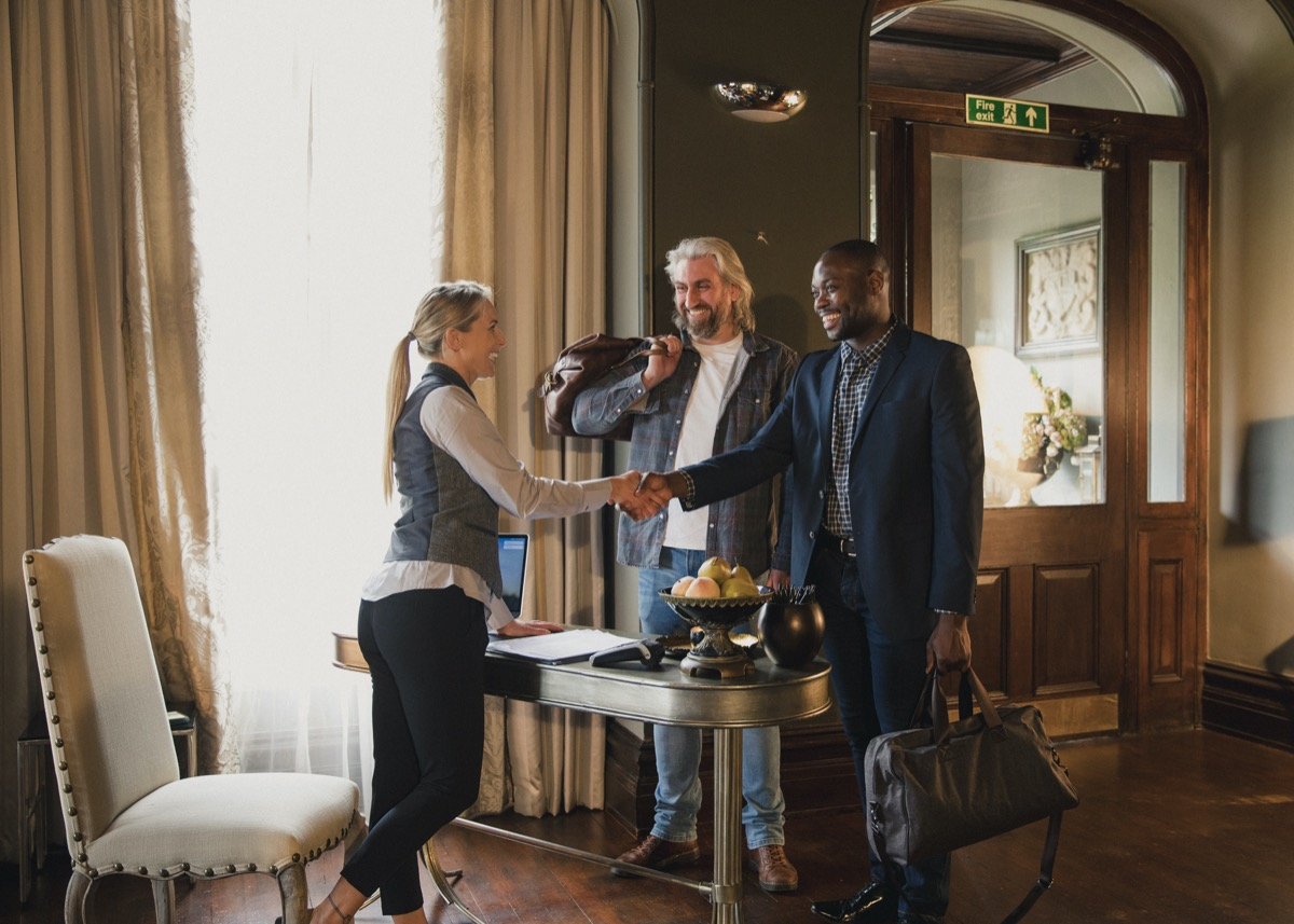 Two men arrive at their luxury hotel where they are staying. They greet the hotel receptionist and pay for their stay.