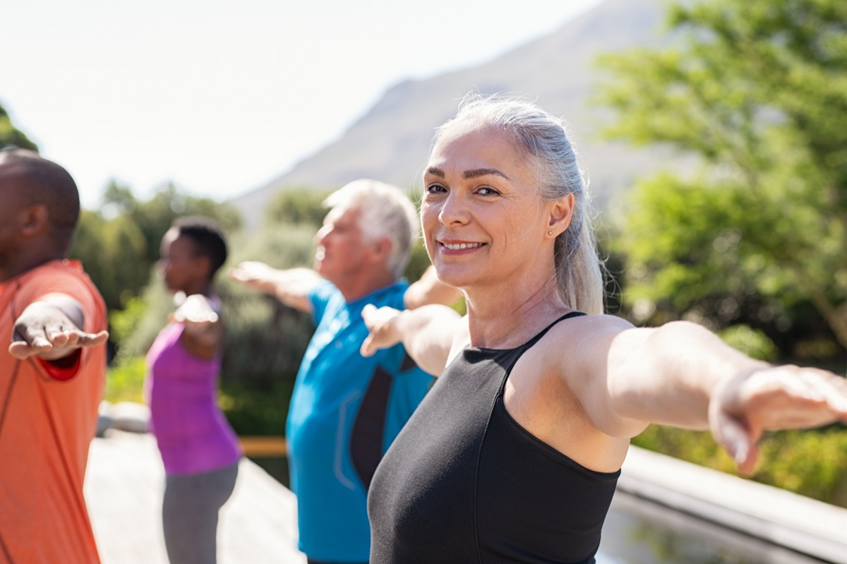 Portrait of happy senior woman practicing yoga outdoor with fitness class. Beautiful mature woman stretching her arms and looking at camera outdoor. Portrait of smiling serene lady with outstretched arms at park. (Portrait of happy senior woman pract