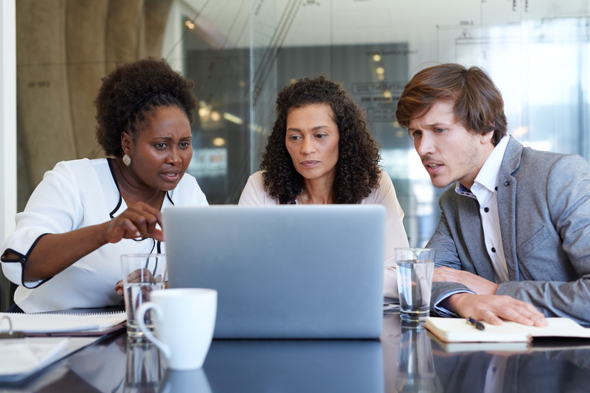 confused group of business workers staring at a screen