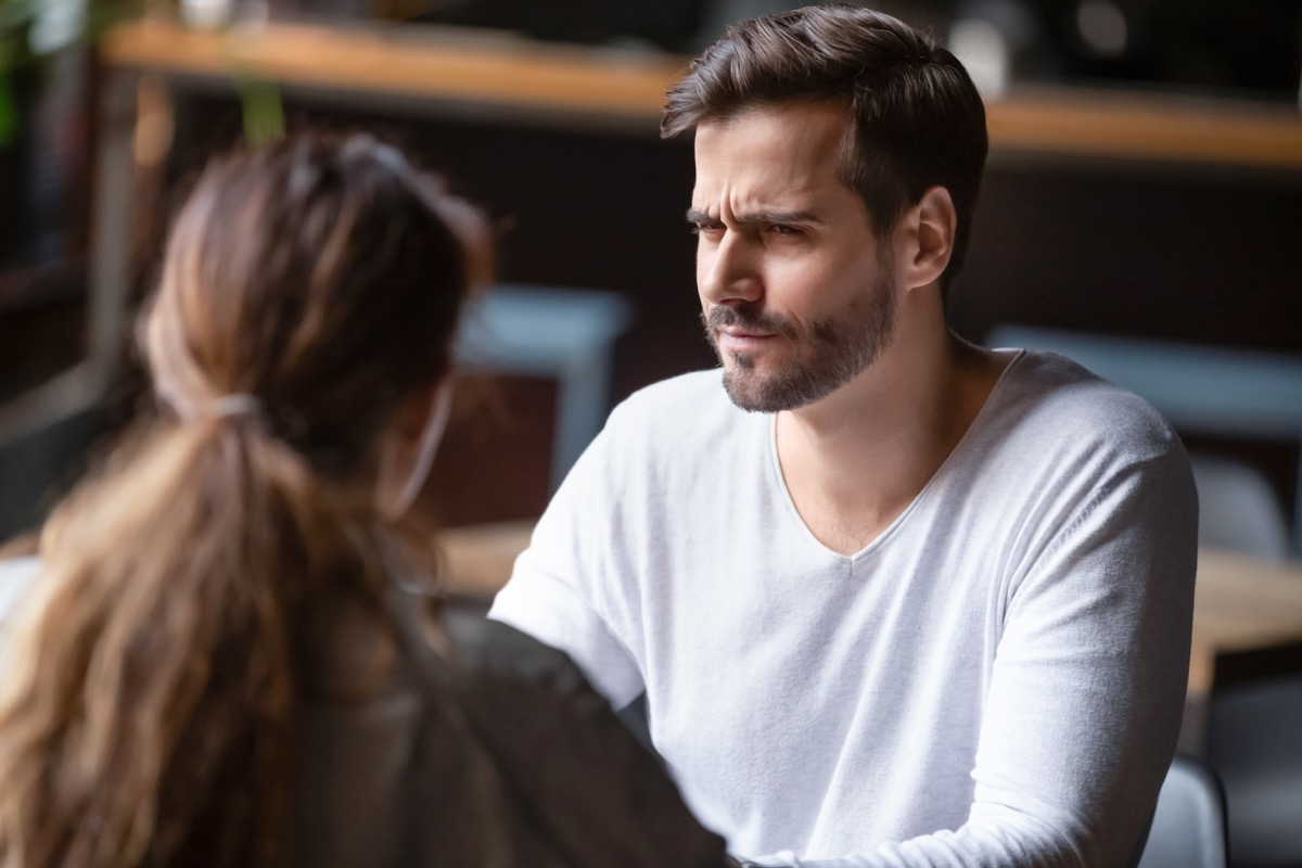 Doubting dissatisfied man looking at woman, bad first date concept, young couple sitting at table in cafe, talking, bad first impression, new acquaintance in public place, unpleasant conversation
