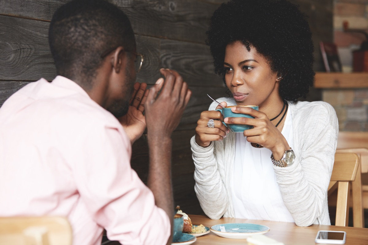 Couple talking over coffee in shop